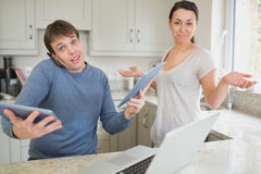 Busy man using two tablets and laptop with wife holding hands up Royalty Free Stock Photos