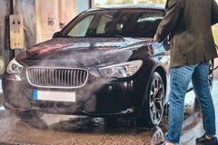 Busy man is washing his own car at car washing station. royalty free stock image