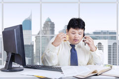 Busy man working while eating in office Stock Images