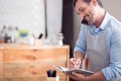 Busy man writing something down. Your order , please. Cropped image of smiling man making some notes while taking an order Stock Photography