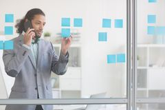 Busy manager. Young businessman talking by smartphone and reading notes of working points on transparent office board Stock Photography