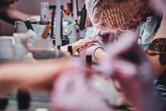 Busy manicure studio with a lot of working staff and clients. Very busy manicure studio with a lot of working staff and clients stock photography