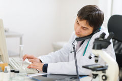 Busy medical speaking phone and working on pc. Busy medical doctor speaking phone and working on pc Stock Photography