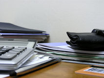 Busy and messy. A busy desk against a wall, shot from low angle. Books, papers, calculator, pencil, wallet,watch, bank card royalty free stock images