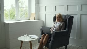 Busy middle aged woman working with a laptop. Career orientated. Pleasant middle aged woman sitting in the arm chair while working with a laptop and being stock footage