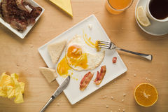 Busy morning bacon and eggs, orange juice and tea. Concept of a standard everyday breakfast. Concept of a busy lifestyle. Bacon and fried eggs, fresh orange Royalty Free Stock Photography