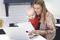 Busy Mother With Baby Coping With Stressful Day At Home. Mother With Baby Coping With Busy Day At Home Stock Photography