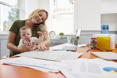 Busy Mother With Baby Running Business From Home Stock Images