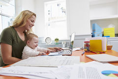 Busy Mother With Baby Running Business From Home Royalty Free Stock Photography