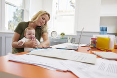Busy Mother With Baby Running Business From Home Royalty Free Stock Images