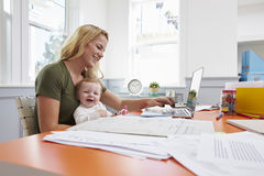 Busy Mother With Baby Running Business From Home Stock Photography