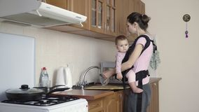Busy mother with baby in sling at home washing dirty dishes 4k stock video