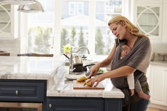 Busy Mother With Baby In Sling Multitasking At Home Royalty Free Stock Images
