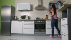 Busy mother cooking in kitchen holding baby son stock video