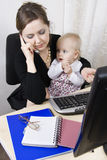 Busy mother with her baby. Busy mother holding her baby royalty free stock image
