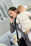 Busy mother holding her baby and talking on the phone Royalty Free Stock Photo