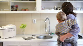 Busy Mother in Kitchen. Beautiful young mother holding a baby and doing kitchen work, cooking