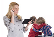 Busy mother with tablet and mobile while her children fighting Royalty Free Stock Images