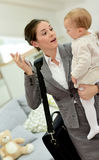 Busy mother talking to her baby and on the phone stock photography