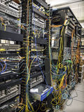 Busy network racks. Network rack in data center with busy cablings Stock Images