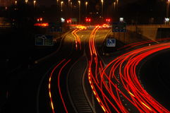 Busy Off Ramp. Traffic speeds past a motorway junction at night Royalty Free Stock Images