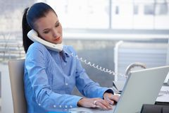 Busy office girl working with phone and computer. Busy office worker girl taking landline phone call while typing on laptop computer royalty free stock images