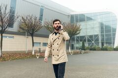 Free Busy Office Manager Is Late. Walking Near Industrial Buildings, Talking On He Phone Royalty Free Stock Photos - 174587078