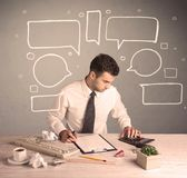 Busy office worker with drawn text bubbles Royalty Free Stock Image