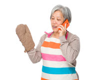 Busy old lady with kitchen apron and talk to mobile phone Stock Photos