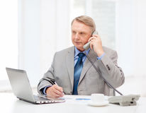 Busy older businessman with laptop and telephone. Business, technologym communication and office concept - busy older businessman with laptop, charts, coffee and Stock Photography