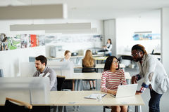 Busy open plan office. Interior of busy open plan office: male and female workers sitting at their desks, Afro-American superior discussing business project with Stock Photo