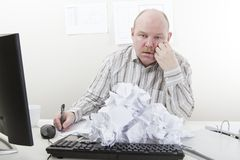 Overworked and Tired Businessman. Busy and overworked office worker with a heap of paper at the office desk. To much work Royalty Free Stock Photography