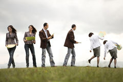 Busy people on the move. Busy business people on a hill looking and filling documents Royalty Free Stock Photography