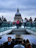 Busy people walking down the street. Busy people walking down the street and an isolated girl wearing a pink  coat stopped and thinking.  Millenium bridge Royalty Free Stock Photo
