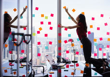 Busy Person Attaching Many Sticky Notes On Large Window Stock Photography