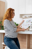 Busy pregnant woman working with prints royalty free stock photo