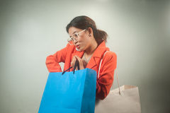 Busy young Asian business woman with shopping bags on a background. Royalty Free Stock Photo
