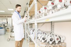 Busy quality control engineer examining manometers in warehouse. Serious concentrated bearded quality control engineer in lab coat reading document and examining Royalty Free Stock Images