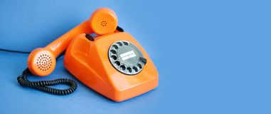 Busy retro phone orange color, handset receiver on blue background. copy space stock photo