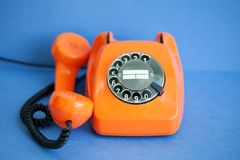 Busy retro phone orange color, handset receiver on blue background. Shallow depth field photography. Royalty Free Stock Photos