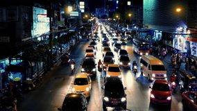 Busy Road Through City At Night. Vibrant night scene of main road through city lit up with neon lights stock footage