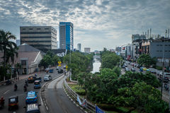 Busy roads in Jakarta. Buildings along the river in Indonesian capital Royalty Free Stock Photography
