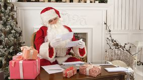 Busy Santa Claus checking Christmas letters sitting at his table. Professional shot on Lumix GH4 in 4K resolution. You can use it e.g. in your commercial video Stock Images