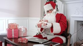 Busy Santa Claus preparing presents using laptop and digital tablet, sorting his letters and receiving a gift from a. Little girl. Timelapse shot. Professional Royalty Free Stock Photography