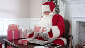 Busy Santa Claus preparing presents using laptop and digital tablet, sorting his letters and receiving a gift from a. Little girl. Timelapse shot. Professional stock video footage