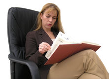 Busy schedule. Woman sitting in an executive chair going thru her schedule Royalty Free Stock Photography