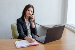 Busy secretary is answering call and writing memo at the same time Stock Photography