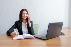 Busy secretary is answering call and writing memo at the same time Royalty Free Stock Photography