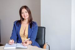 Busy secretary is answering call and writing memo at the same time.  stock image