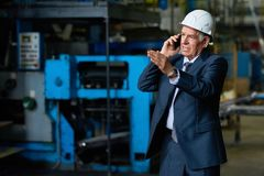 Busy Senior Entrepreneur Using Smartphone. Confident senior entrepreneur wearing suit and hardhat talking to his colleague on smartphone while walking along Stock Photos